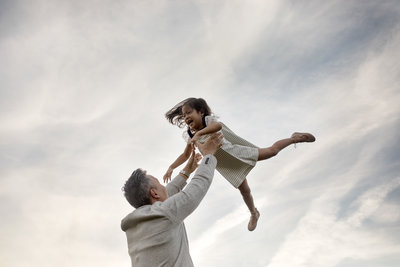 Family photographer Elle Baker photography captures child and father playing during outdoor lifestyle session