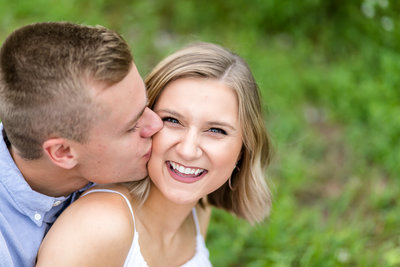 groom kissing bride cheek outdoor engagement session