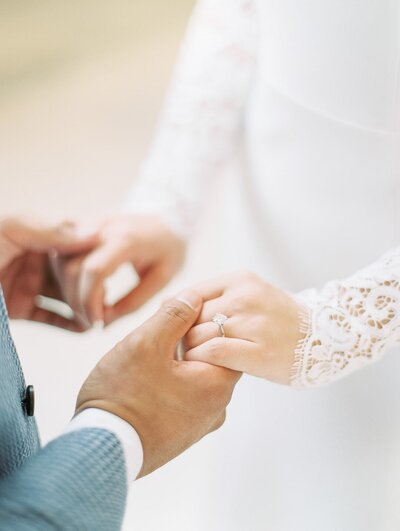 Close up of wedding couple holding hands at ceremony with bride in long-sleeved lace gown and groom in blue houndstooth suit.