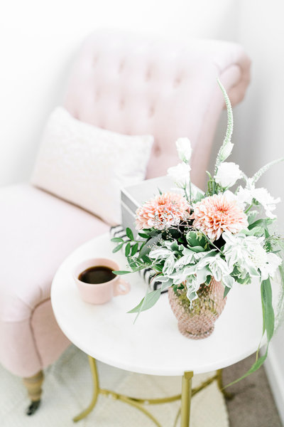Pink upholstered chair next to white side table with flowers and coffee