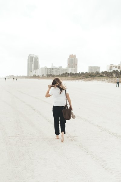 Woman walking on white sand beach