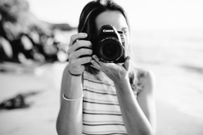 Black and white portrait of a photographer holding up her Canon 5D Mark IV camera
