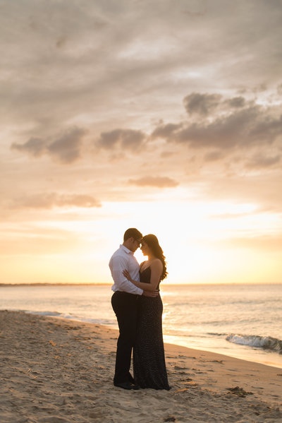 couple hugging on beach at sunset in virginia beach