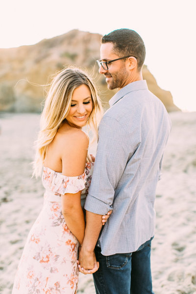 beautiful engaged couple smiling at each other at the beach in laguna beach ca