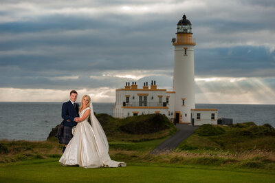 Bride and groom at Turnberry wedding with the lighthouse behind them, photographed by wedding photographers in Glasgow.