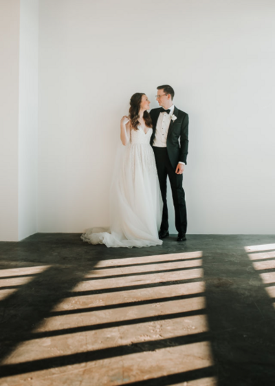 A black tie tuxedo groom and lace and tulle wedding gown