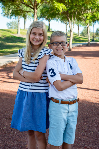 Brother and sister lean back to back with their arms crossed as they pose for a family photo.
