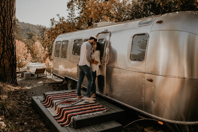 man and woman leaning against airstream trailer