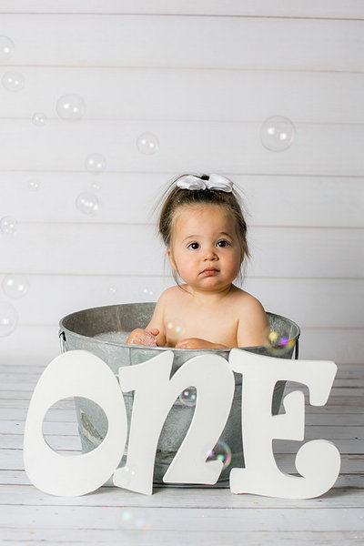 One year old little girl takes bubble bath in portrait studio