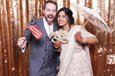 couple holding best photo booth props