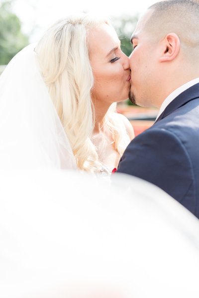 Bride and groom kiss while veil blows.