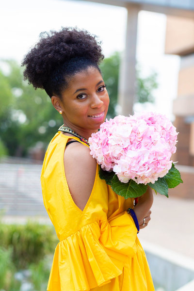 African American Woman Holding Pink Flowers