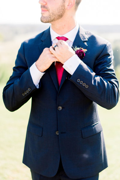 groom in a dark blue suit adjusting his red tie at foxhall resort atlanta wedding photographer lane albers photography