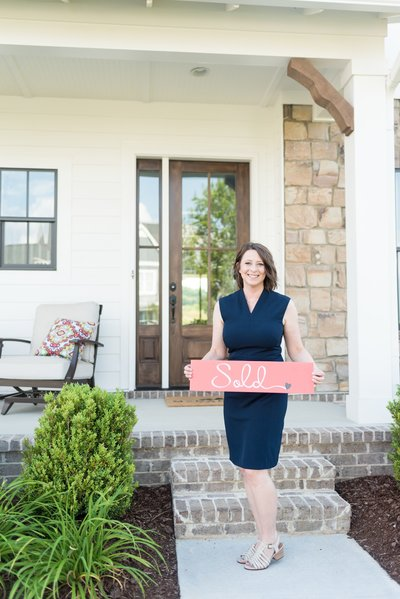 "Realtor in a navy dress holding a red sign that says ""sold"" outside of a Nashville home"