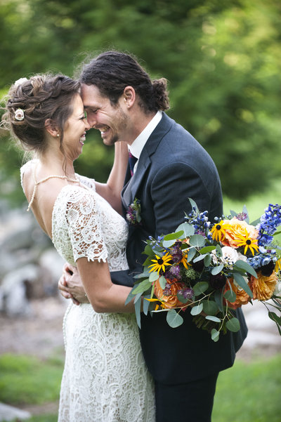 Bride & groom embrace while holding bridal bouquet & smile brightly after wedding in Otisfield, Maine