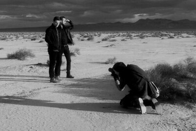 black and white Behind the scenes Mark Maryanovich photographing duo Polarcode standing in desert