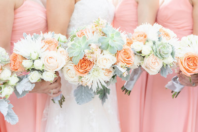 Coral bridesmaid dresses and peach, cream, coral, and greenery bridal bouquets captured by best NJ wedding photographer Diana & Korey Photo and Film