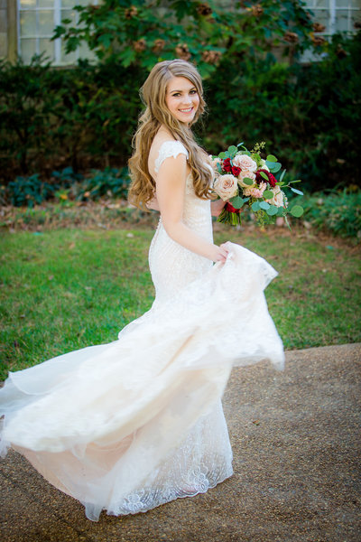Bride holding her bouquet of flowers twirling in her dress at Burritt on the Mountain