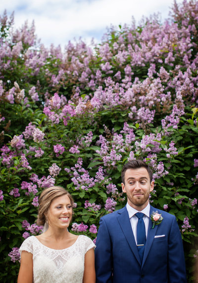 A bride and groom are standing in front of a lilac bush, glancing at each other.