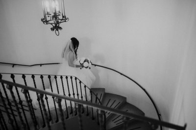 bride walks down grand staircase on way to ceremony