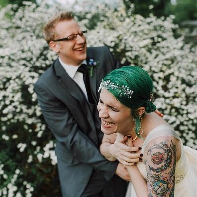 green haired tattooed bride in white gown and metal flower crown laughs with groom in grey suit in front of a bush at their backyard wedding shot by wedding photographer in philadelphia alex medvick