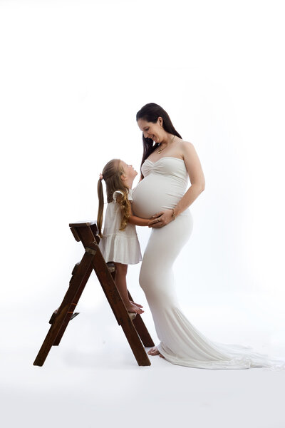 Professional portrait in-studio, pregnant mother with daughter on ladder