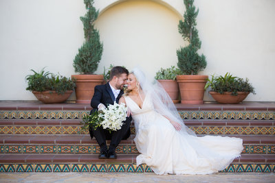 Bride and Groom sitting on Spanish Style Stairs at Estancia