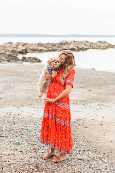 pregnant woman kissing her dog on a beach