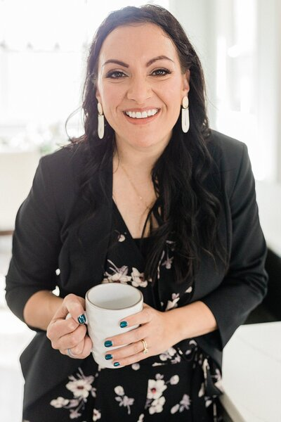 Dolly A Nashville Based Branding and Family Photographer is smiling at the camera and wearing a black blazer for her headshots