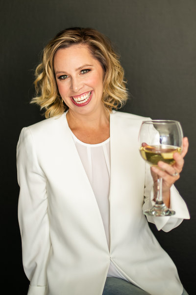 Female business owner in white blazer toasts a glass of wine during portrait photography session