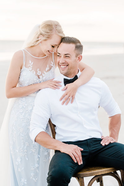 Bride smiles and embraces her groom around the shoulders as he sits in wooden chair on the beach