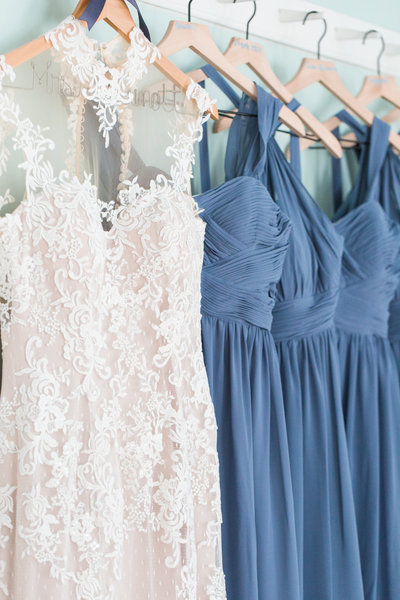 Wedding dress and bridesmaid dresses hanging on wooden hangers in a row