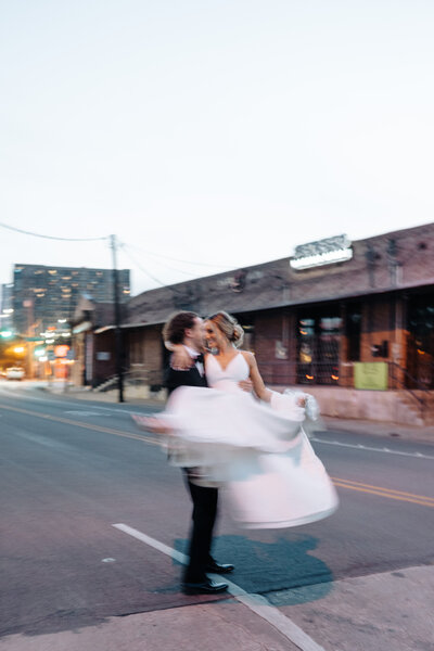 bride and groom spinning in the road
