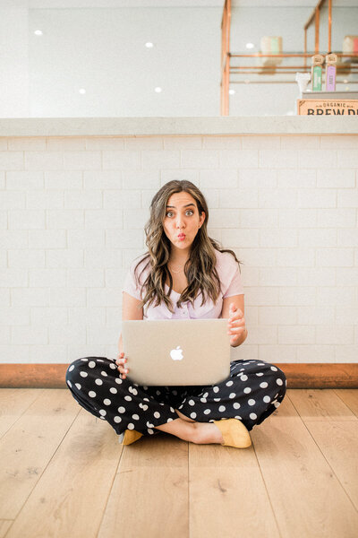 Emmy de Leon Jones sitting on a wide plank natural wood floor and working at her MacBook