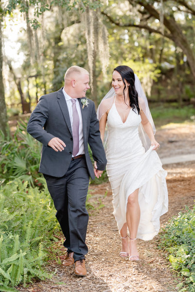 Bride and groom hold hands while running through nature on their wedding day
