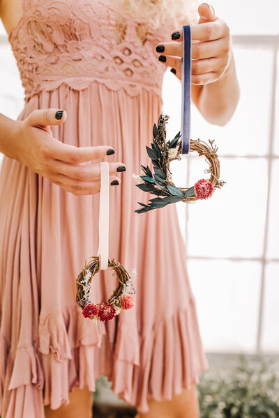 girl holding two miniature dried floral wreathes