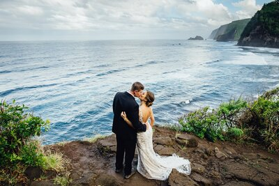 bride and groom kiss on a cliff