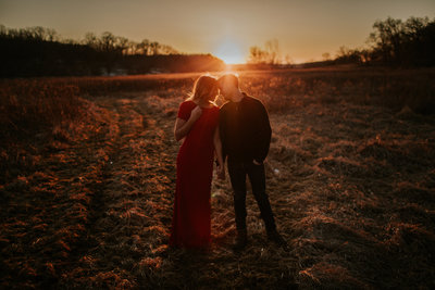 Wisconsin couple holding hands, leaning in for kiss during their Rustic Wisconsin  Sunset Engagement Session.