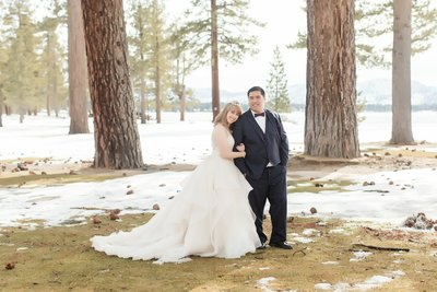 Bride & groom picture in snow. Black suite forrest background, wedding in Lake Tahoe.  Photographed by Bakersfield wedding photographer Marianne Lucas