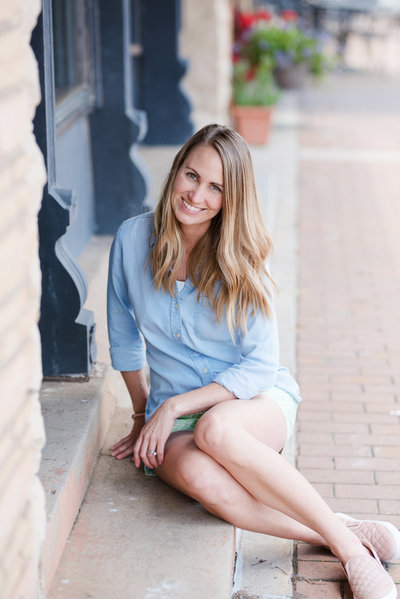 Photographer Amanda Zabrocki smiles in blue blouse sitting on steps outside beautiful blue building