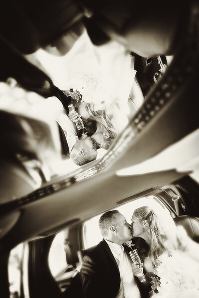 An artistic shot of a bride and groom kissing inside a limo.
