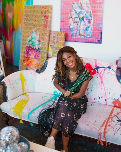 Photographer sitting on paint splattered couch with red flowers
