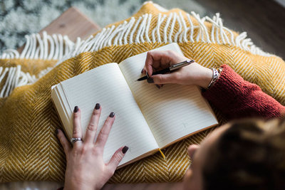 woman writing in journal with yellow blanket