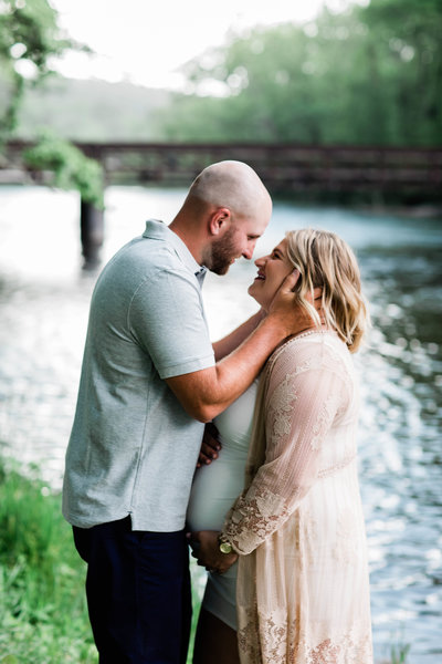 Bald man with beard pulling in pregnant woman with blonde hair in for a kiss in front of a river