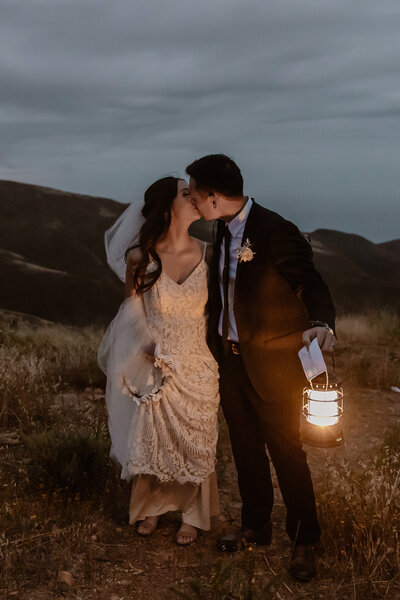 bride and groom kissing with lantern