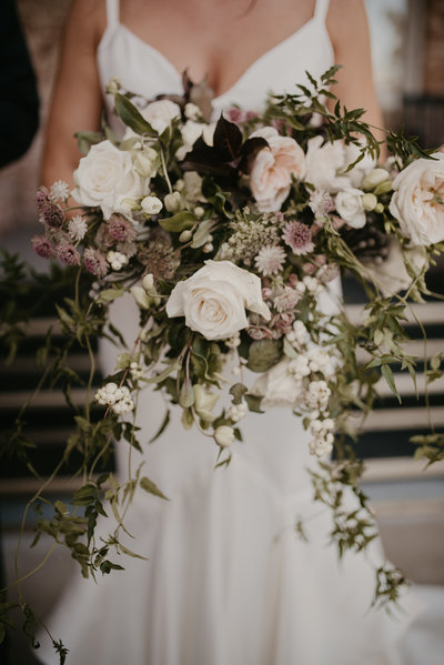 Bride holds her modern fall bouquet at her Northwest Arkansas Wedding