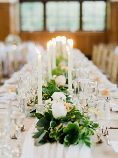 White and green florals paired with the glow of taper candles accent long hardwood tables at this luxurious Staten Island wedding.