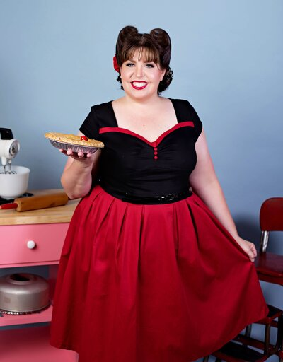 brunette pinup girl in a red and black dress holding a cherry pie  in a pinup picture