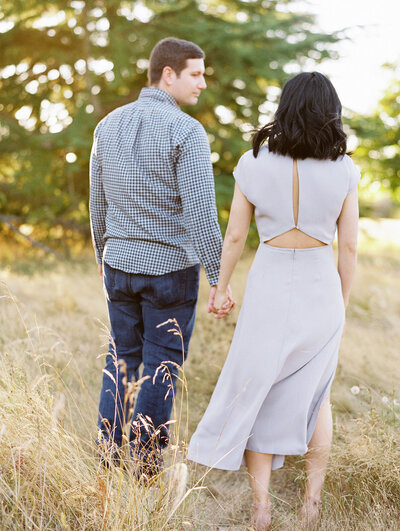 Engaged couple walk away from camera hand in hand with sun setting in the surrounding trees