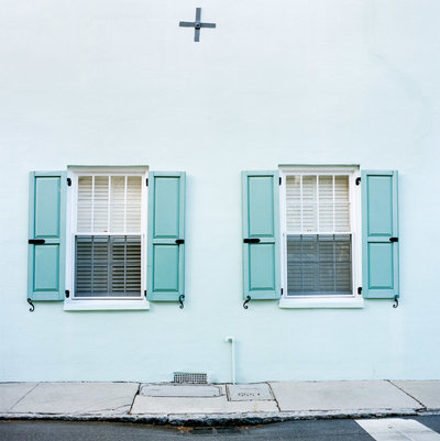 A light blue Rainbow Row print of a home with two windows with blue shutters in Charleston, SC